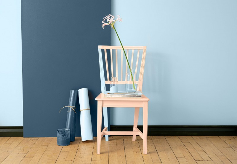light pink beige chair in front of blue wall