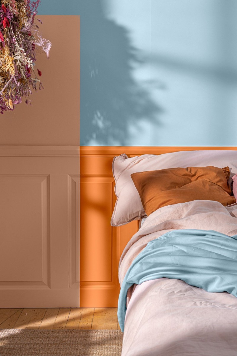 bedroom with blue colour wall and different orange shades on bed headboard